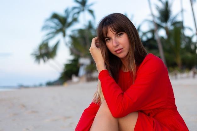 일몰 열 대 하얀 모래 해변에 낭만적 인 행복 분위기에 빨간 여름 드레스에 백인 여자