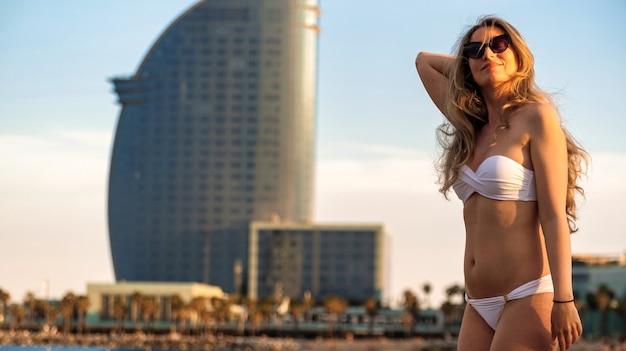 Кавказская женщина в солнцезащитных очках и купальнике позирует на побережье средиземного моря, испания