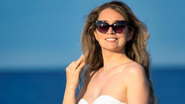 Кавказская женщина в солнцезащитных очках позирует на фоне средиземного моря, испания