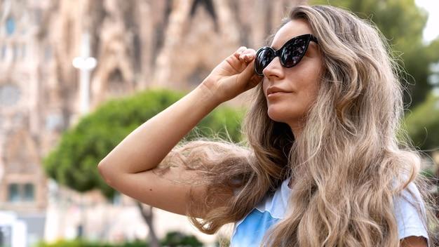 Кавказская женщина в солнцезащитных очках позирует с саграда фамилия на заднем плане в барселоне, испания