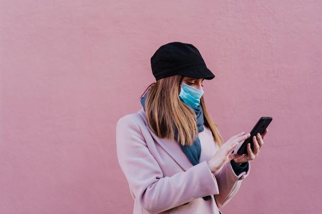 防護マスクを着用し、携帯電話を使用して通りの白人女性。コロナウイルスの概念