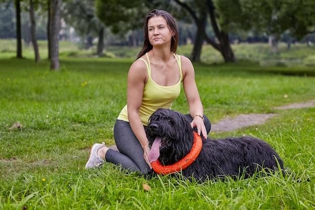 그가 걷는 동안 공공 공원에서 잔디에 누워있는 동안 백인 여자는 검은 briard입니다
