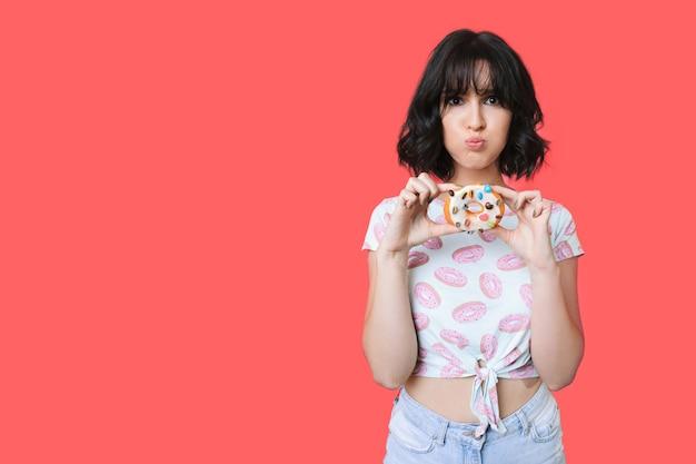여유 공간이있는 빨간 스튜디오 벽에 맛있는 도넛을 들고 백인 여자가 재미있는 얼굴을하고있다.