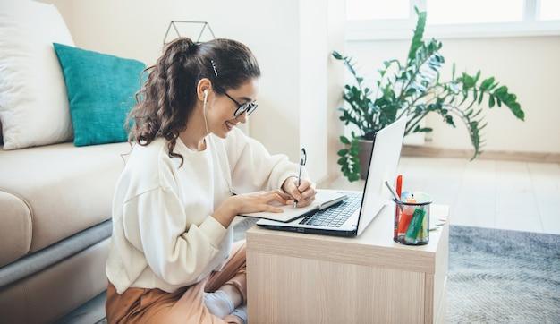 Кавказская женщина делает онлайн-уроки на ноутбуке, улыбаясь, когда что-то пишет, сидя на полу