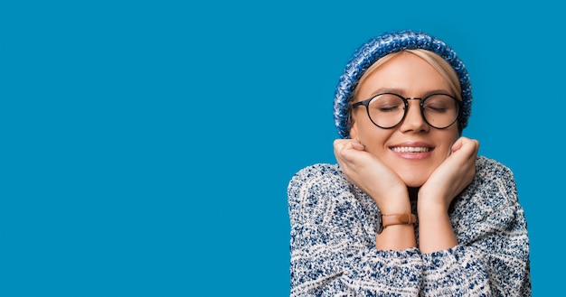 Caucasian woman is dreaming about something posing with a warm hat on a blue wall with free space
