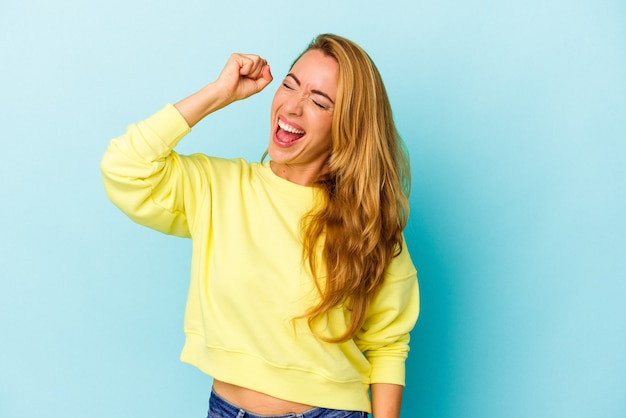 Caucasian woman isolated on blue background celebrating a victory, passion and enthusiasm, happy expression.