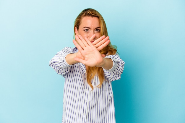 Caucasian woman isolated on blue background doing a denial gesture