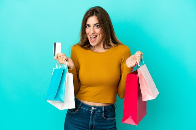 Caucasian woman isolated on blue background holding shopping bags and surprised