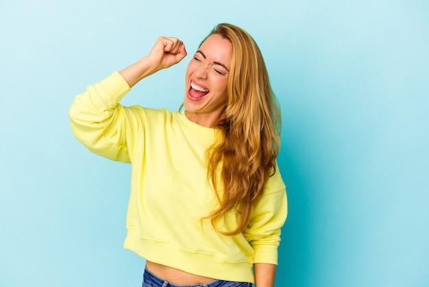 勝利、情熱と熱意、幸せな表現を祝う青い背景に孤立した白人女性。