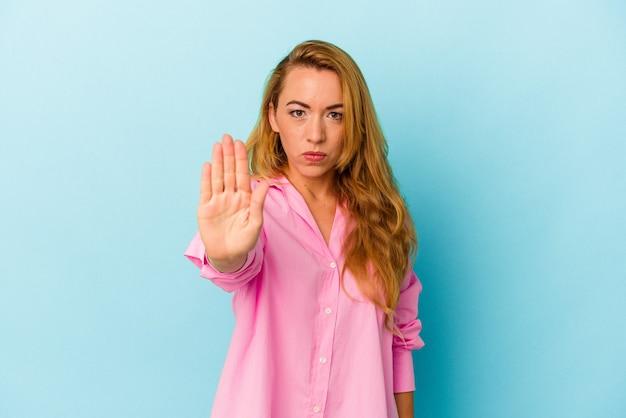 파란색 배경에 격리된 백인 여성이 정지 신호를 표시하고 뻗은 손으로 서 있는 것을 방지합니다.