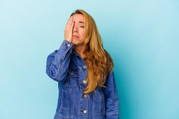 青い背景に孤立した白人女性は疲れていて、頭に手を置いて非常に眠いです。
