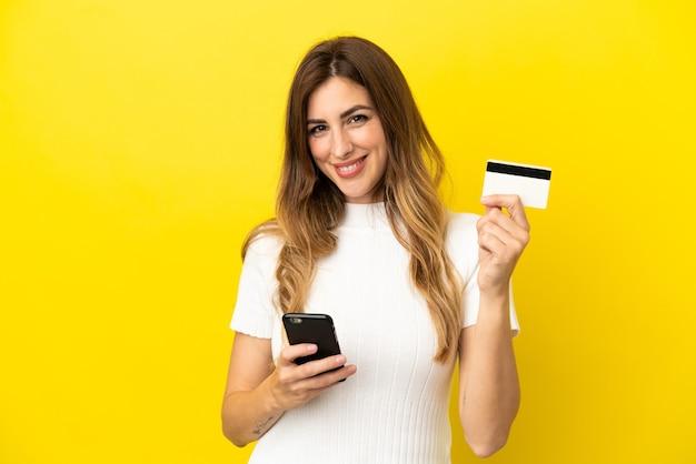 신용 카드로 모바일로 구매하는 노란색 배경에 고립 된 백인 여자