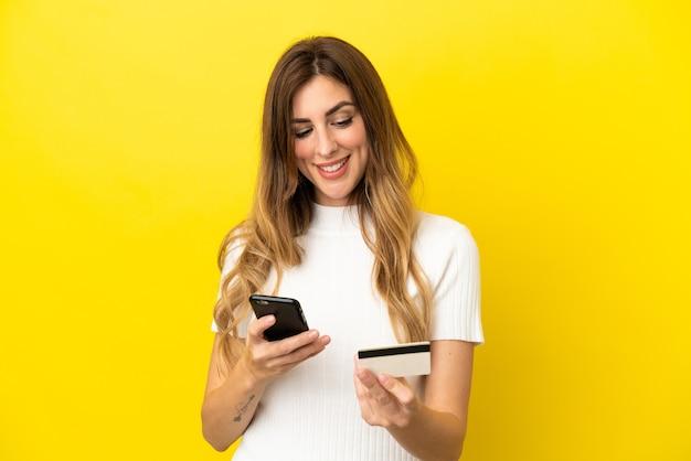 신용 카드로 모바일로 구매하는 노란색 배경에 고립 된 백인 여성