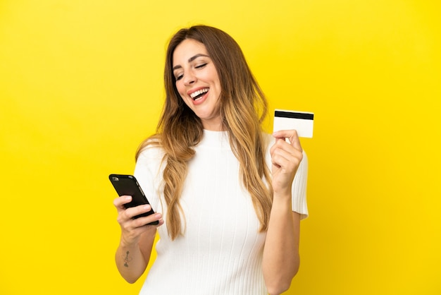 Кавказская женщина, изолированные на желтом фоне, покупает с мобильного с помощью кредитной карты