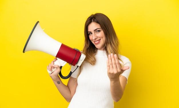 Кавказская женщина изолирована на желтом фоне держит мегафон и приглашает прийти с рукой