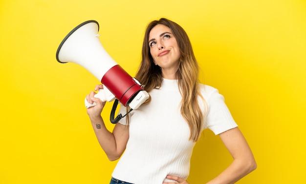 Кавказская женщина изолирована на желтом фоне держит мегафон и думает