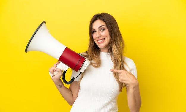 Кавказская женщина изолирована на желтом фоне с мегафоном и с удивленным выражением лица