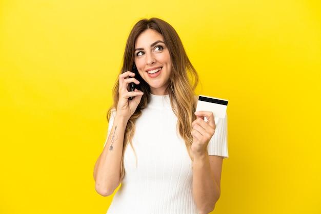 휴대 전화와 대화를 유지하고 신용 카드를 들고 노란색 배경에 고립 된 백인 여자