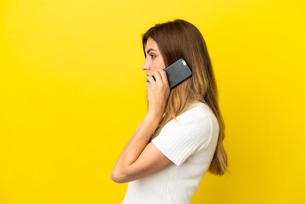 누군가와 휴대 전화로 대화를 유지하는 노란색 배경에 고립 된 백인 여자