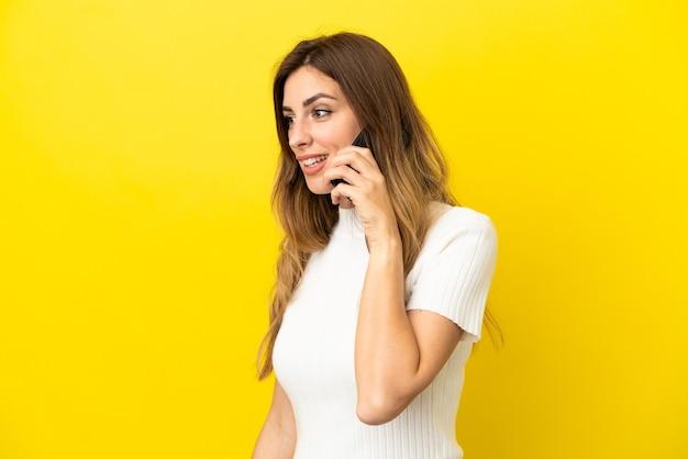 Кавказская женщина изолирована на желтом фоне, разговаривая по мобильному телефону с кем-то