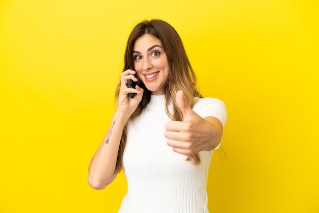 노란색 배경에 격리된 백인 여성이 엄지손가락을 치켜드는 동안 휴대폰과 대화를 유지합니다.