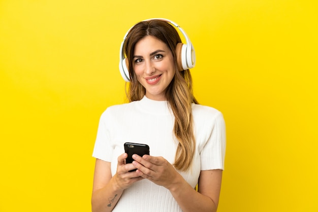 携帯電話で音楽を聴いて正面を向いて黄色の背景に分離された白人女性