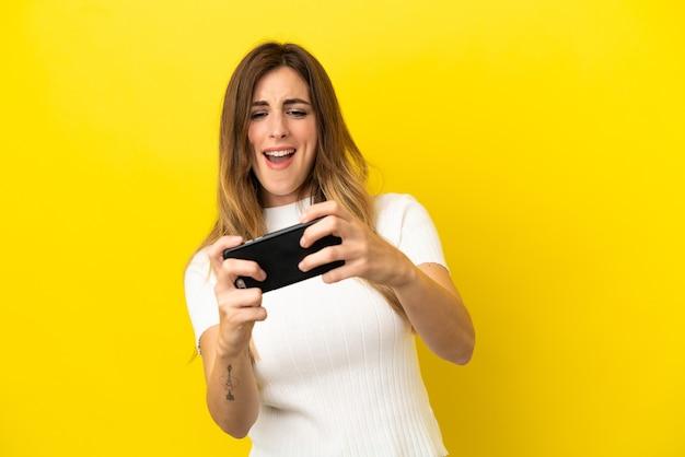 휴대 전화를 가지고 노는 노란색 배경에 고립 된 백인 여자