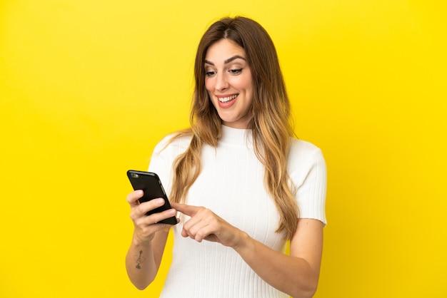 모바일로 메시지 또는 이메일을 보내는 노란색 배경에 고립 된 백인 여자