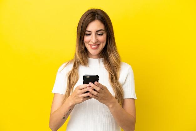 노란색 배경에 격리된 백인 여성이 모바일로 메시지나 이메일을 보냅니다.