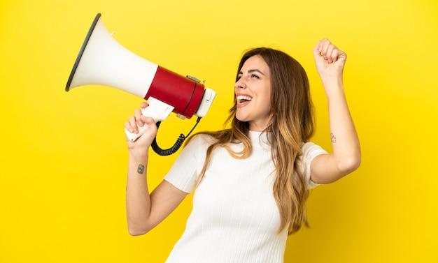 Кавказская женщина, изолированная на желтой стене, кричит в мегафон, чтобы объявить что-то в боковом положении