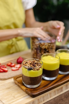 Caucasian woman in kitchen makes chia puddings with mango jam. desert made of almond milk, chia seeds, cocoa, mango jam and granola.