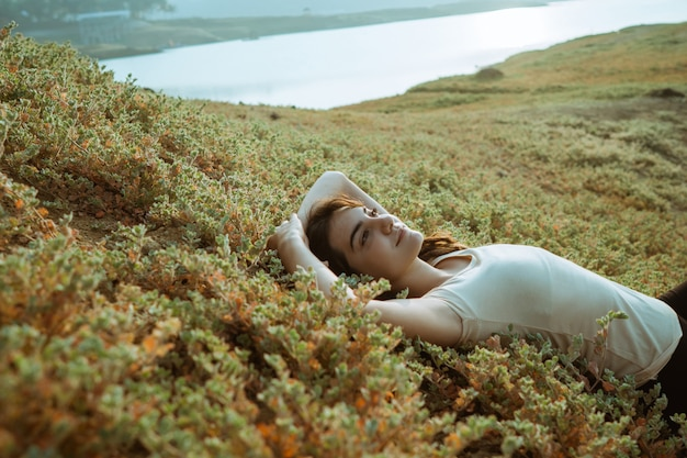 Caucasian woman laying by a lake with blanket