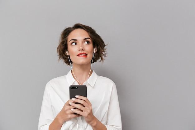 灰色の壁に隔離されたイヤホンを介してスマートフォンで音楽を聴いている白人女性