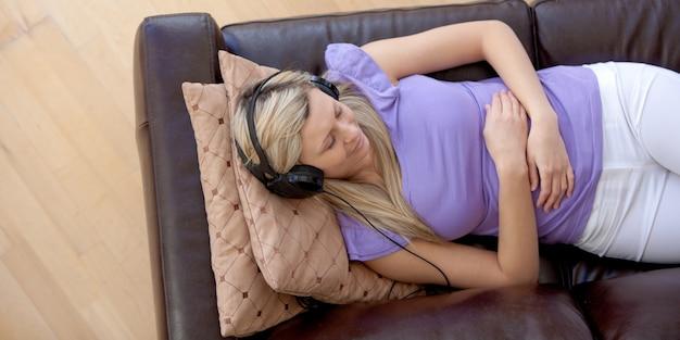 ソファで音楽を聴く白人女性