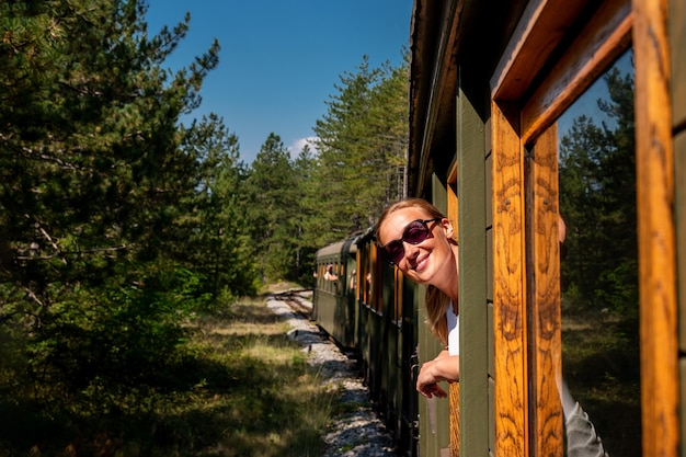 電車の窓から外を眺める白人女性
