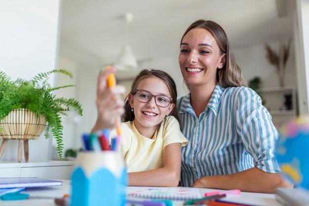 ホームスクーリング中に娘を誇りに思って絵を描いている白人女性。