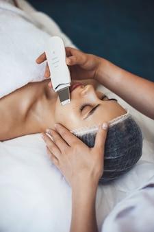Кавказская женщина, лежа в спа-салоне в медицинской шапочке, пока косметолог использует аппарат на ее лице