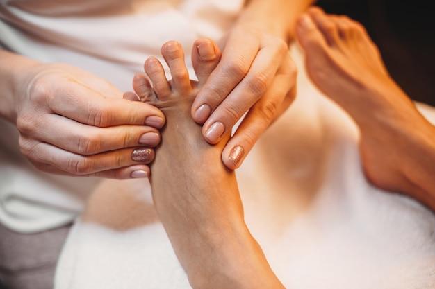 Caucasian woman lying at the spa salon and having a leg massage procedure