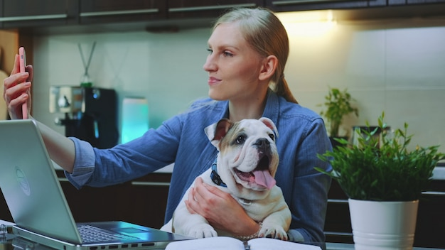 Caucasian woman making selfie with a small dog while sitting at the computer