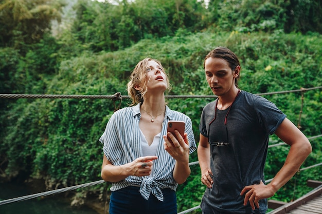 Caucasian woman and man having a bad cellular signal in the nature travel problem concept
