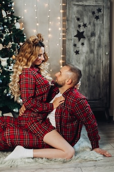 Caucasian woman and man relaxes on the floor in the living room in christmas atmosphere together.