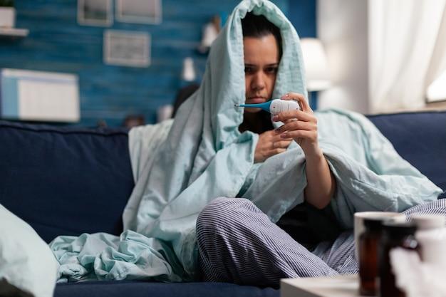 Donna caucasica che misura la temperatura malata a casa con un termometro. persona che si sente male al freddo, che controlla la febbre e i sintomi dell'infezione influenzale della malattia. adulto a riposo con mal di testa