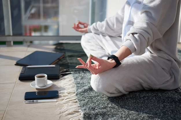 Caucasian woman meditating on balcony in pajamas before working on digital tablet as a freelancer