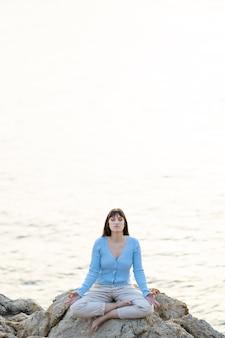 평상복 차림으로 바다 앞에서 명상하는 백인 여성