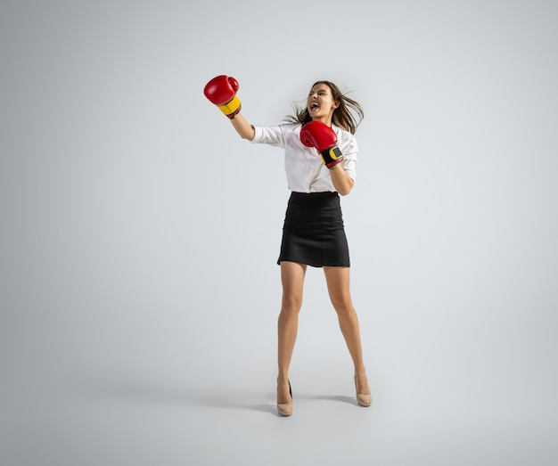 Caucasian woman in office clothes boxing on grey