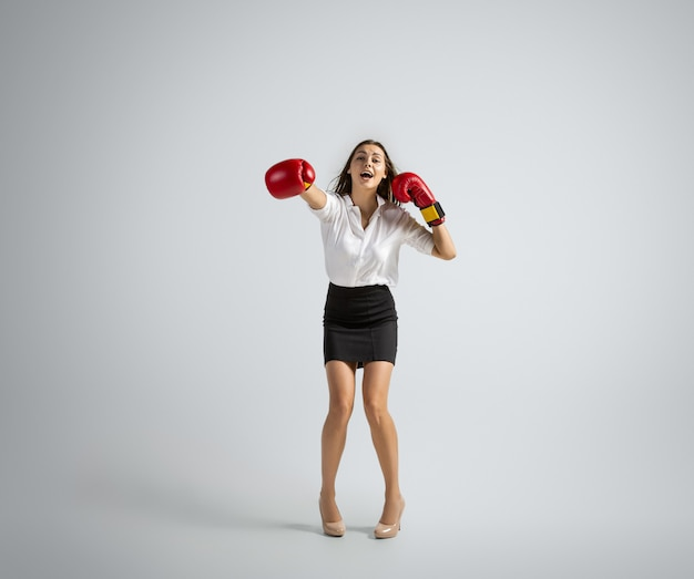 Caucasian woman in office clothes boxing isolated on grey  wall