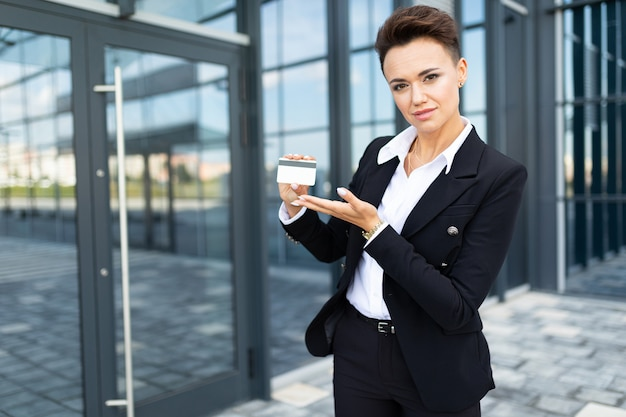 Caucasian woman in office clothes holds a credit card and near the office building