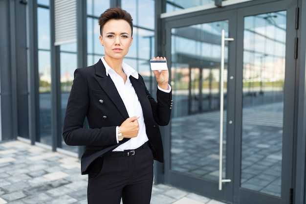 Caucasian woman in office clothes holds a little white house and near the office building