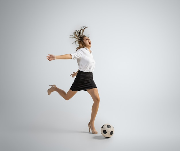Caucasian woman in office clothes kicking ball on grey