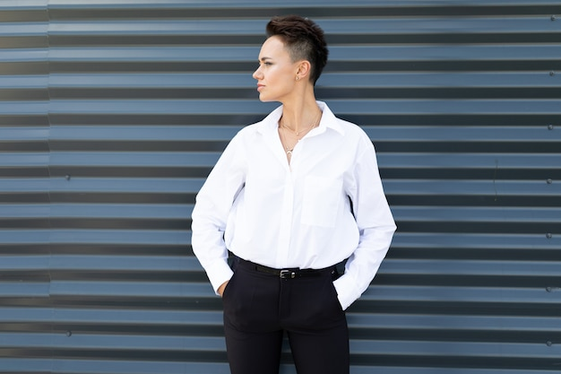 Caucasian woman in office clothes near the office building